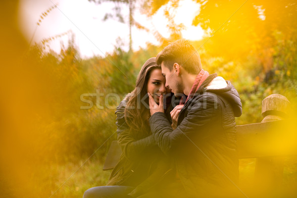 Loving couple in the autumn park sitting on a bench Stock photo © Geribody