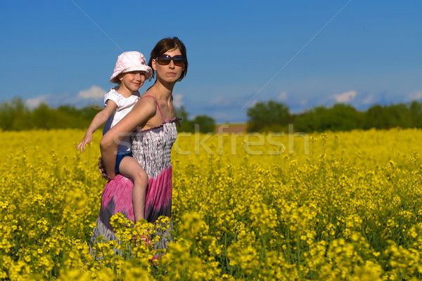 Young mother and her daughter having fun at the colza field  Stock photo © Geribody