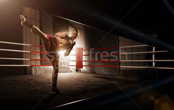 Young man kickboxing in the Arena Stock photo © Geribody