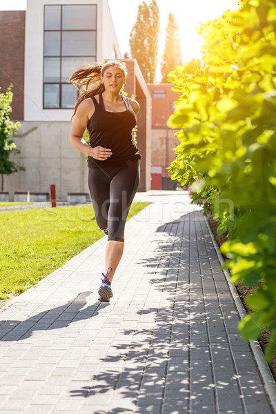 Running woman in black sport outfit on the sidewalk  Stock photo © Geribody