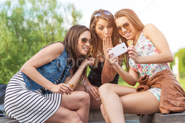 3 beautiful girlfriend watch the funny photos taken at  Stock photo © Geribody