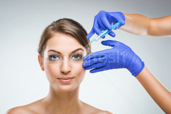 Beautiful woman with plastic surgery, plastic surgeon hands Stock photo © Geribody