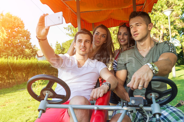 Four young people in a four-wheeled bicycle, they do selfie Stock photo © Geribody