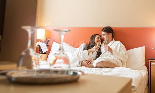Mosolyog pár pezsgő szemüveg ágy férfi Stock fotó © Geribody