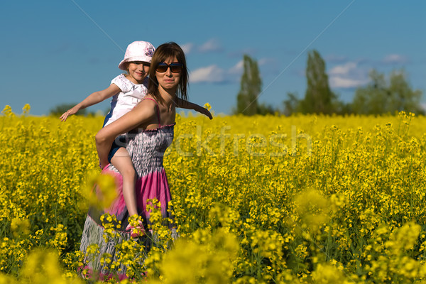 Mother and her daughter having fun at the colza field Stock photo © Geribody