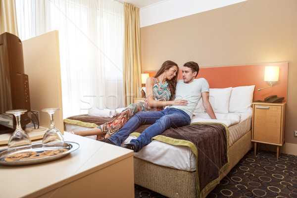 Young couple's arrival to the hotel, sitting on the bed  Stock photo © Geribody