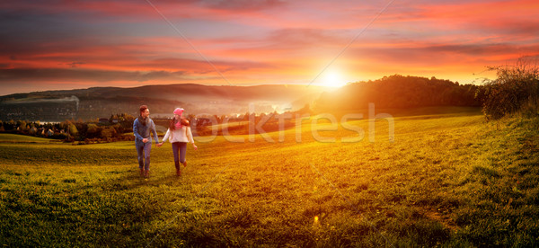 Stock photo: Loving couple holding hands running on the field. beautiful landscape