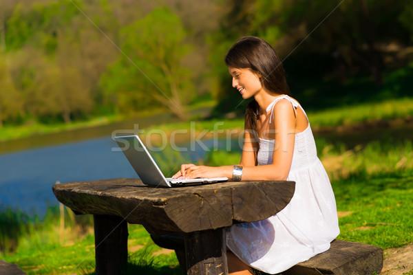 Sevimli genç kadın dizüstü bilgisayar oturma güzel Stok fotoğraf © Geribody