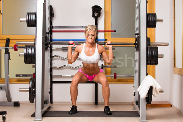 Woman lifts dumbbells in sport centre to develop muscles Stock photo © Geribody