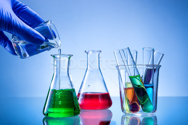 Laboratory equipment, bottles, flasks with color liquid, hand poured Stock photo © Geribody