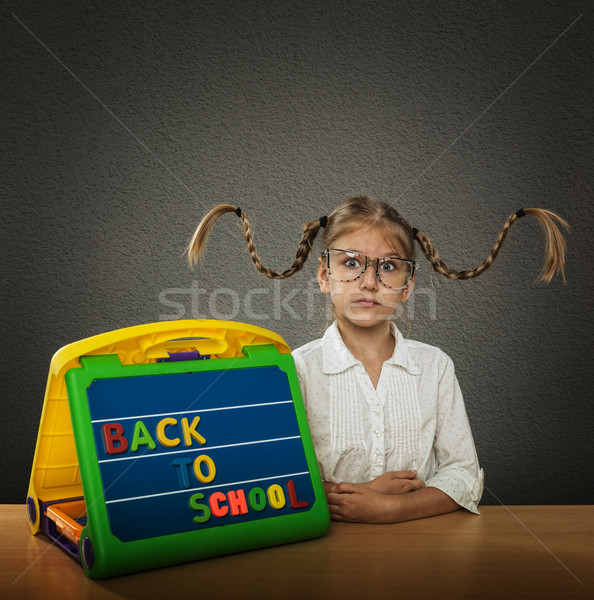 Funny little girl with braided hair up, big glasses, beside her plate Back to School subtitles