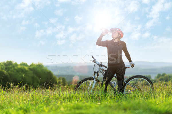 Stock photo:  Sport bike woman , drinking on a meadow , beautiful landscape