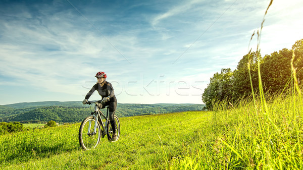 Sport bike woman in a beautiful meadow, fabulous scenery  Stock photo © Geribody