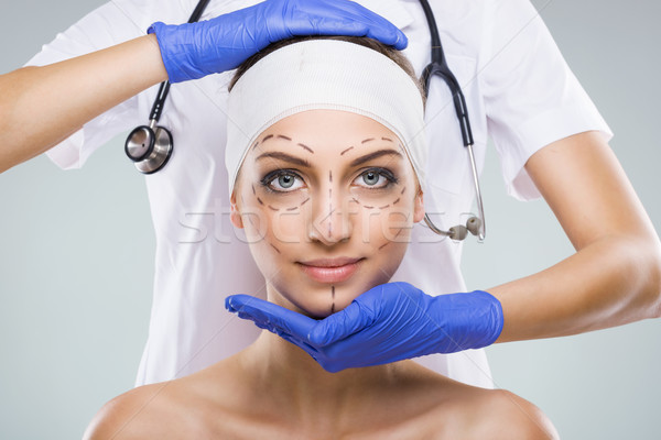 Beautiful woman with plastic surgery, depiction, plastic surgeon hands Stock photo © Geribody