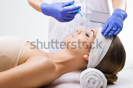 Beautiful woman lying in the clinic, a plastic surgeon in the hands of the needle  Stock photo © Geribody