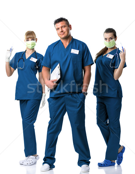 Surgery Team -Doctor, two nurses in blue dress, in mouth mask, with injections and stethoscope Stock photo © Geribody