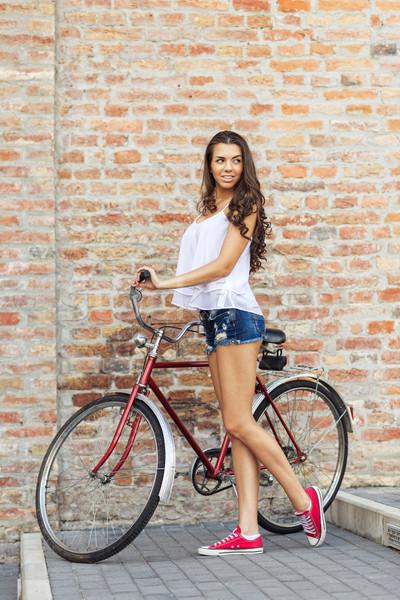 Güzel bir kadın eski bisiklet tuğla duvar kadın şehir Stok fotoğraf © Geribody