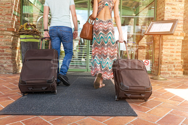 Young couple standing at hotel corridor upon arrival, looking for room, holding suitcases Stock photo © Geribody