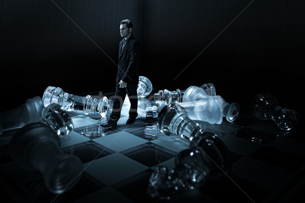 Businessman on a chessboard,walk from the capsized dummies Stock photo © Geribody