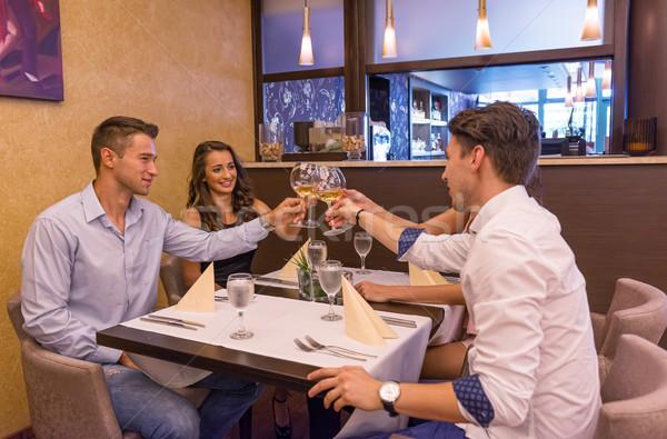 Good friends in the restaurant clink glasses Stock photo © Geribody