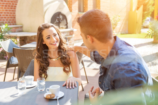 Young couple talking on the terrace of the restaurant, while eating Stock photo © Geribody