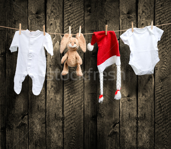 Baby clothes and santa hat on a clothesline, wooden background Stock photo © Geribody