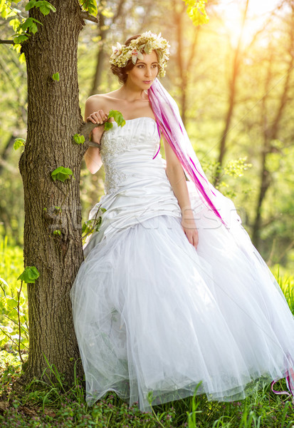 Beautiful bride , flower tiara on her head , relying on the tree Stock photo © Geribody