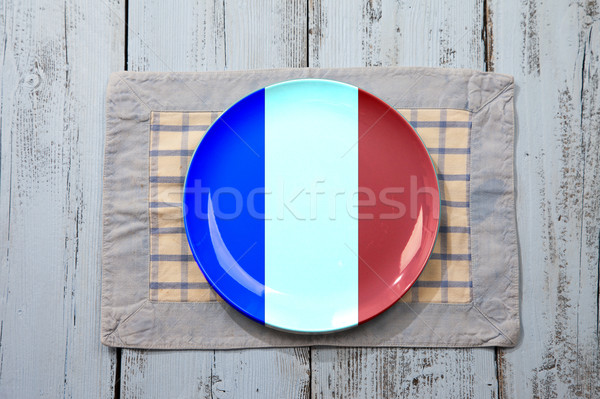 Empty plate with French flag on light blue wooden background Stock photo © gigra