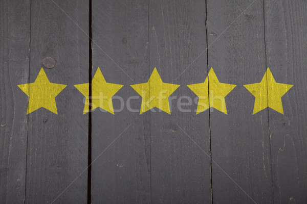 Five yellow ranking stars on black wooden background Stock photo © gigra