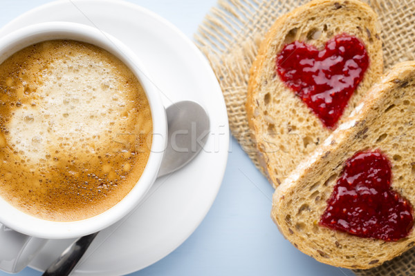 Fresh coffee. Grain slice of bread with jam heart shape. Stock photo © gitusik