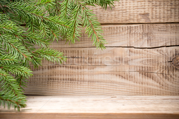 Spruce branch with white braided heart on wooden background. Christmas card. Stock photo © gitusik