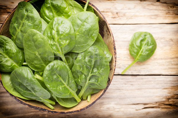 Spinach on the bowl, wooden background. Stock photo © gitusik