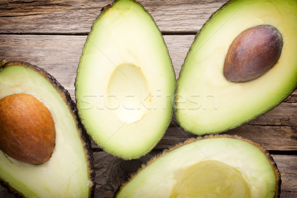 Avocado parts on the wooden table. Stock photo © gitusik