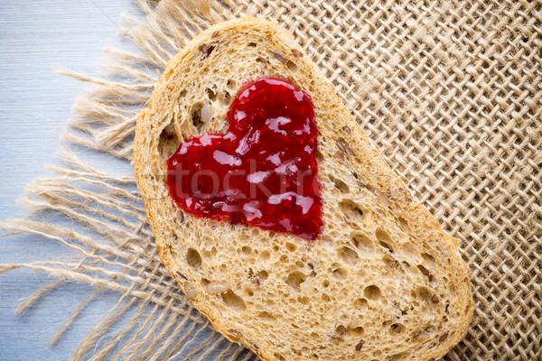 Grain slice of bread with jam heart shape. Stock photo © gitusik