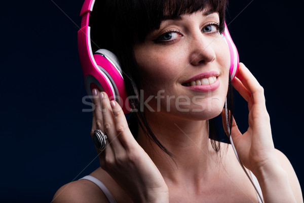 Grinning young adult female using headphones Stock photo © Giulio_Fornasar