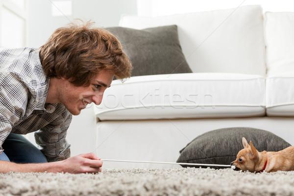 Uśmiechnięty młody człowiek wojny psa w dół Zdjęcia stock © Giulio_Fornasar