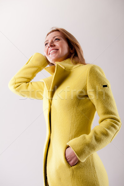 real woman in yellow coat smiling Stock photo © Giulio_Fornasar