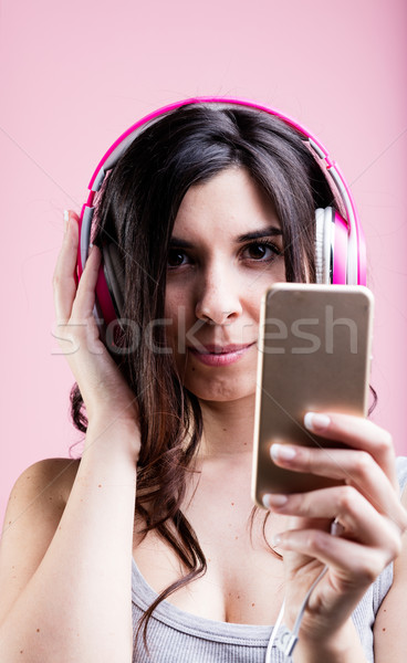 woman listening to music using a smartphone and her pink headphones: portrait on pink background Stock photo © Giulio_Fornasar