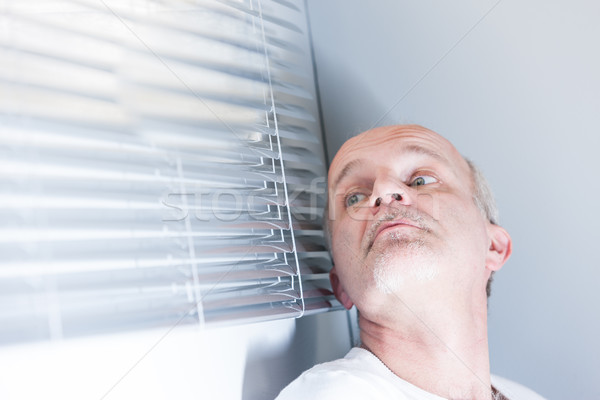 Stock photo: man checking out of the blinds