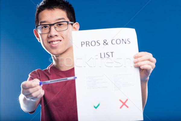 happy asian guy showing a pros and cons list Stock photo © Giulio_Fornasar