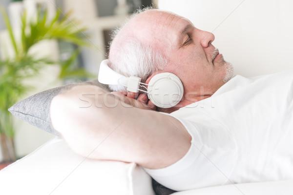 Homem maduro relaxante música sofá mãos atrás Foto stock © Giulio_Fornasar