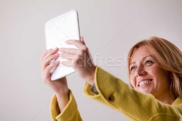 pretty blonde woman using a tablet Stock photo © Giulio_Fornasar