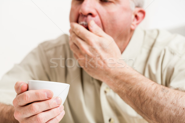 Cropped head and shoulders of yawning man with cup Stock photo © Giulio_Fornasar