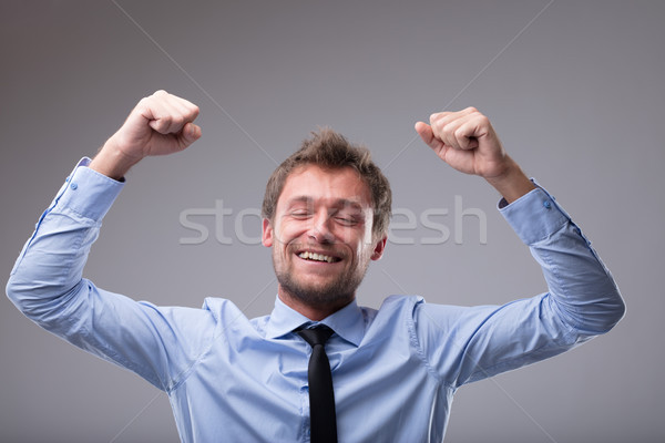 Jubilant happy man cheering and punching the air Stock photo © Giulio_Fornasar