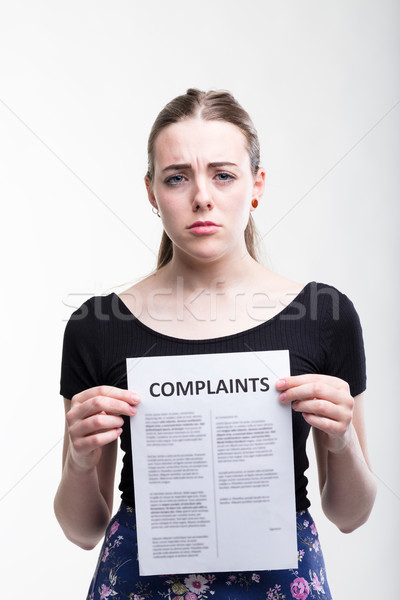 Sad woman holding up a list of complaints Stock photo © Giulio_Fornasar