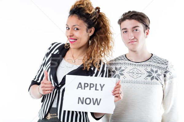 Stock photo: Motivated young woman holding an Apply Now sign