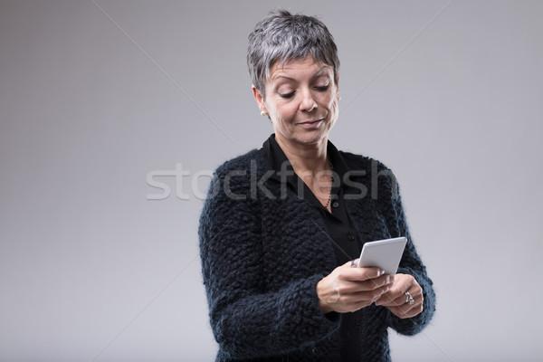 Senior woman reading a text message on a mobile Stock photo © Giulio_Fornasar