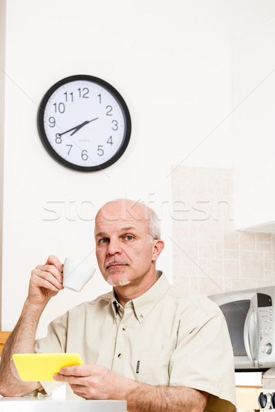Stock photo: Handsome bearded mature man at table with clock