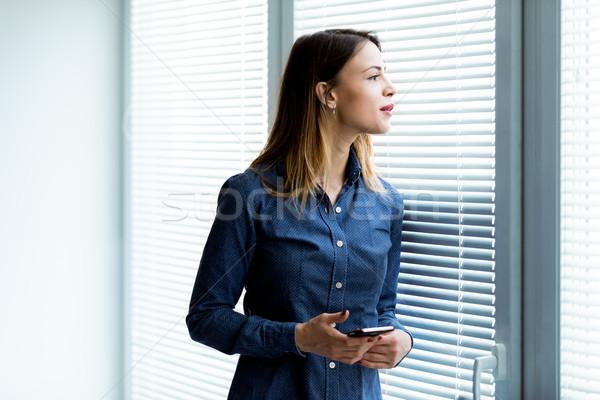 Fiatal nő reluxa özvegy néz valami mobiltelefon Stock fotó © Giulio_Fornasar