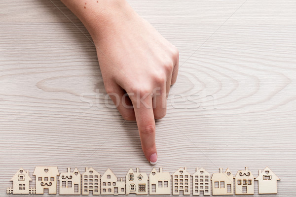 Stock photo: hand pointing out a house among the others mini figures in a mic